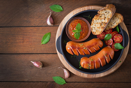 pork sausage: Sausages on the grill with vegetables on a platter. Top view