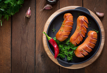 Sausages on the grill pan on the wooden background. Top view 版權商用圖片 - 46014899