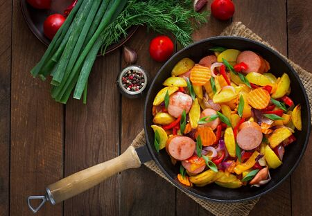 zanahoria: Fried potatoes with vegetables and sausages. Top view Foto de archivo