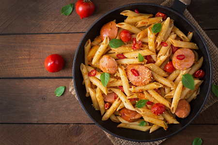 cooked sausage: Penne pasta with tomato sauce with sausage, tomatoes, green basil decorated in a frying pan on a wooden background. Top view Stock Photo