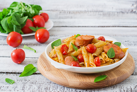 Penne pasta con tomate y salchichas Foto de archivo - 46014965
