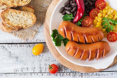 grill: Sausages on the grill with vegetables on a platter. Top view