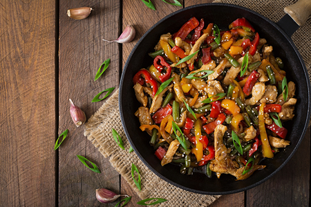 black dish: Stir fry chicken, sweet peppers and green beans. Top view Stock Photo
