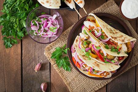 food: Tacos mexicano com frango, legumes grelhados e cebola vermelha. Vista superior
