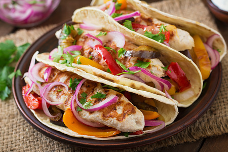 latin food: Mexican tacos with chicken, grilled vegetables and red onion.