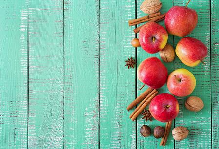 밝은 나무 배경에 잘 익은 빨간 사과와 향신료. 평면도 스톡 콘텐츠