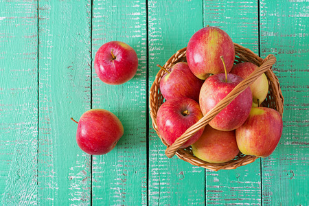 Ripe red apples in a basket on a bright wooden background. Top view