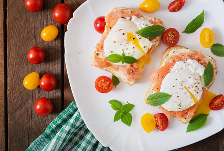 garnish: Sandwich with poached eggs with salmon and cream cheese. Top view Stock Photo