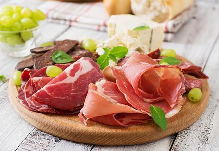 embutidos: Antipasto restauración plato con tocino, cecina, chorizo, queso azul y uvas en un fondo de madera