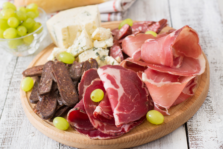antipasto platter: Antipasto catering platter with bacon, jerky, sausage, blue cheese and grapes on a wooden background Stock Photo