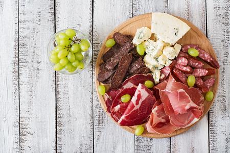 embutidos: Antipasto restauración plato con tocino, cecina, chorizo, queso azul y uvas en un fondo de madera. Vista superior Foto de archivo