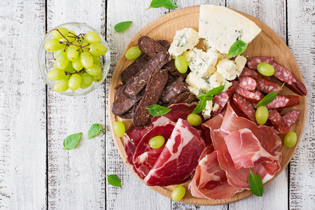 Antipasto catering platter with bacon, jerky, sausage, blue cheese and grapes on a wooden background. Top view