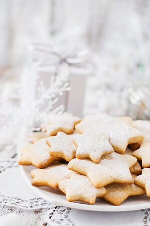 cookies: Christmas cookies and tinsel on a light wooden background