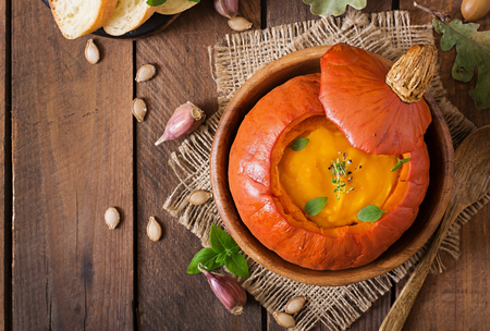 Pumpkin cream soup with peppers and herbs in a pumpkin. Top view