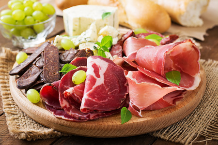 italian salami: Antipasto catering platter with bacon, jerky, sausage, blue cheese and grapes on a wooden background Stock Photo