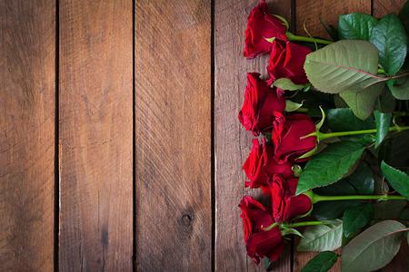 Bouquet di rose rosse su uno sfondo di legno scuro. Vista dall'alto Archivio Fotografico - 47609366