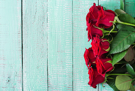 beautiful anniversary: Bouquet of red roses on a light wooden background. Top view