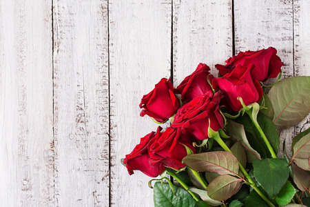 Bouquet of red roses on a light wooden background. Top view