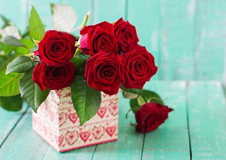 and bouquet: Bouquet di rose rosse su fondo in legno chiaro. Archivio Fotografico