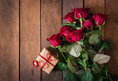 어두운 나무 배경에 빨간 장미 꽃다발. 평면도