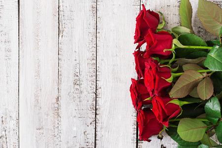Blumenstrauß aus roten Rosen auf einem hellen Hintergrund aus Holz. Aufsicht