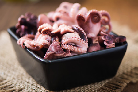 black octopus: Boiled small octopus on a black bowl Stock Photo