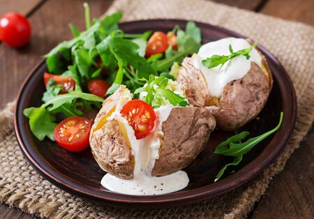 filled: Baked potato filled with sour cream, arugula and tomatoes Stock Photo