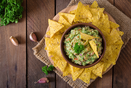 guacamole: Guacamole avocado, lime, tomato, onion and cilantro, served with nachos - Traditional Mexican snack. Top view