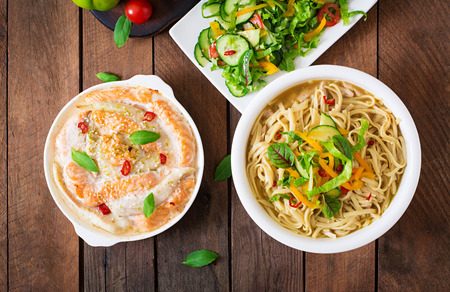 baked: Baked slices of red and white fish with honey and lime juice, served with fresh salad and soft noodles in miso broth. Top view