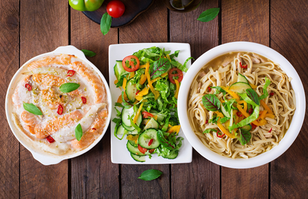 fish sauce: Baked slices of red and white fish with honey and lime juice, served with fresh salad and soft noodles in miso broth. Top view