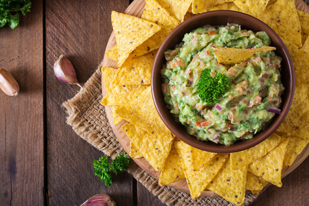 nachos: Guacamole avocado, lime, tomato, onion and cilantro, served with nachos - Traditional Mexican snack. Top view