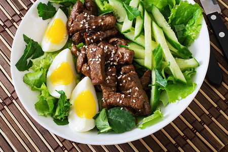 asian style: Salad with spicy beef, cucumber and eggs in the Asian style. Stock Photo