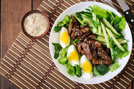 plates of food: Salad with spicy beef, cucumber and eggs in the Asian style. Top view