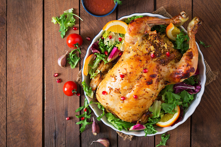 salads: Baked chicken stuffed with rice for Christmas dinner on a festive table. Top view.