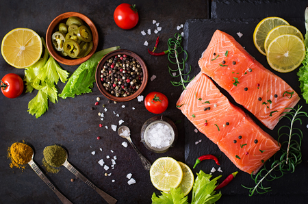 black stones: Raw salmon fillet and ingredients for cooking on a dark background in a rustic style. Top view