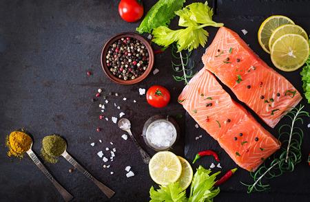 원시 연어 등심 및 소박한 스타일의 어두운 배경에 요리 재료. 평면도 스톡 콘텐츠