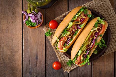 comida rapida: Perrito caliente con pepinillos, tomate y lechuga en el fondo de madera. Vista superior