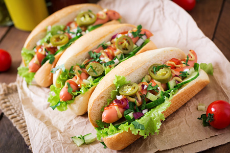 hot peppers: Hot dog with jalapeno peppers, tomato, cucumber and lettuce on wooden background