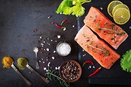 especias: Filete de salmón crudo y los ingredientes para cocinar sobre un fondo oscuro en un estilo rústico. Vista superior