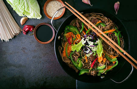 noodles: Soba noodles with beef, carrots, onions and sweet peppers. Top view
