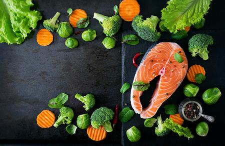mariscos: filete de salm�n crudo y los ingredientes para cocinar sobre un fondo oscuro en un estilo r�stico. Vista superior Foto de archivo