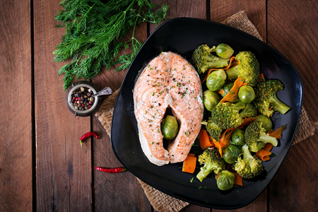 Cooked on steam salmon steak with vegetables. Top view