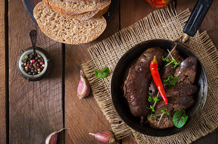 offal: Homemade blood sausage with offal on the old wooden background in rustic style. Top view