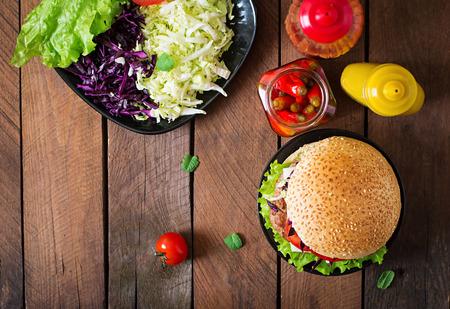 Panino hamburger con hamburger succosa, formaggi e mix di cavolo. Vista dall'alto Archivio Fotografico - 49938464