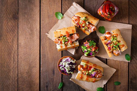 large dog: Hot dog - sandwich with Mexican salsa on wooden background. Top view