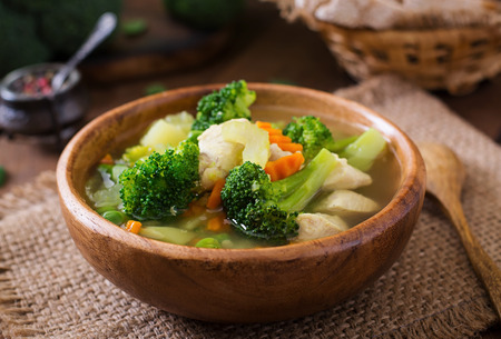 Chicken soup with broccoli, green peas, carrots and celery in  bowl on a wooden background in rustic style Stockfoto