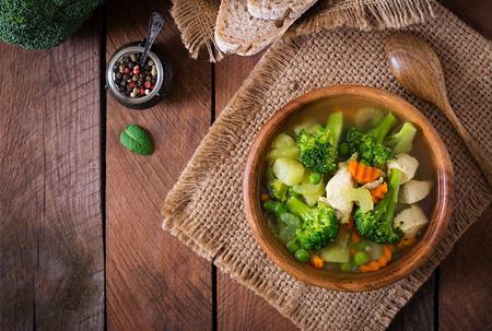 comiendo pan: Sopa de pollo con br�coli, guisantes, zanahorias y apio en un recipiente en un fondo de madera en estilo r�stico. Vista superior