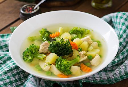 Sopa de pollo con brócoli, guisantes, zanahorias y apio en un plato blanco sobre un fondo de madera en estilo rústico Foto de archivo