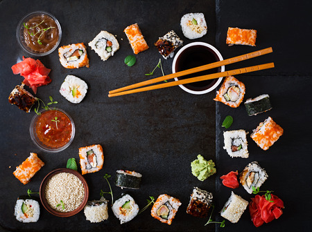 Traditional Japanese food - sushi, rolls and sauce on a dark background. Top view 스톡 콘텐츠