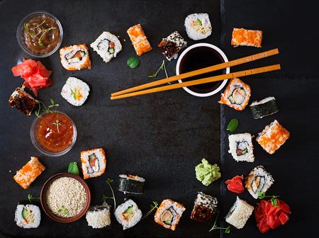 Traditionelles japanisches Essen - Sushi, Brötchen und Soße auf einem dunklen Hintergrund. Aufsicht